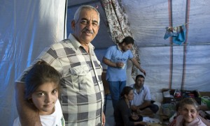 Nissan with his granddaughter and other family members in their tent in Erbil.