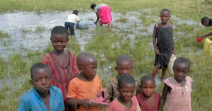 Burundian children are fetching water from a pond formed by the leakage of a pipeline in a settlement area in Uganda.