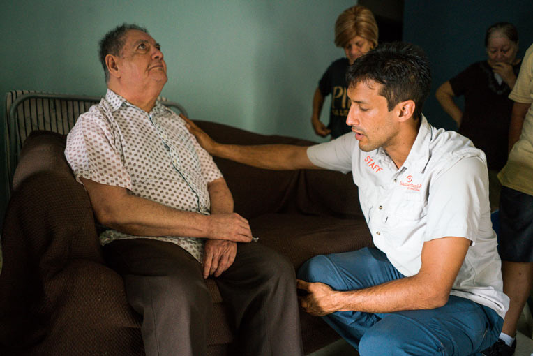 Andres Morales prays with Eugenio Rodriguez  who received a generator from Samaritan's Purse.