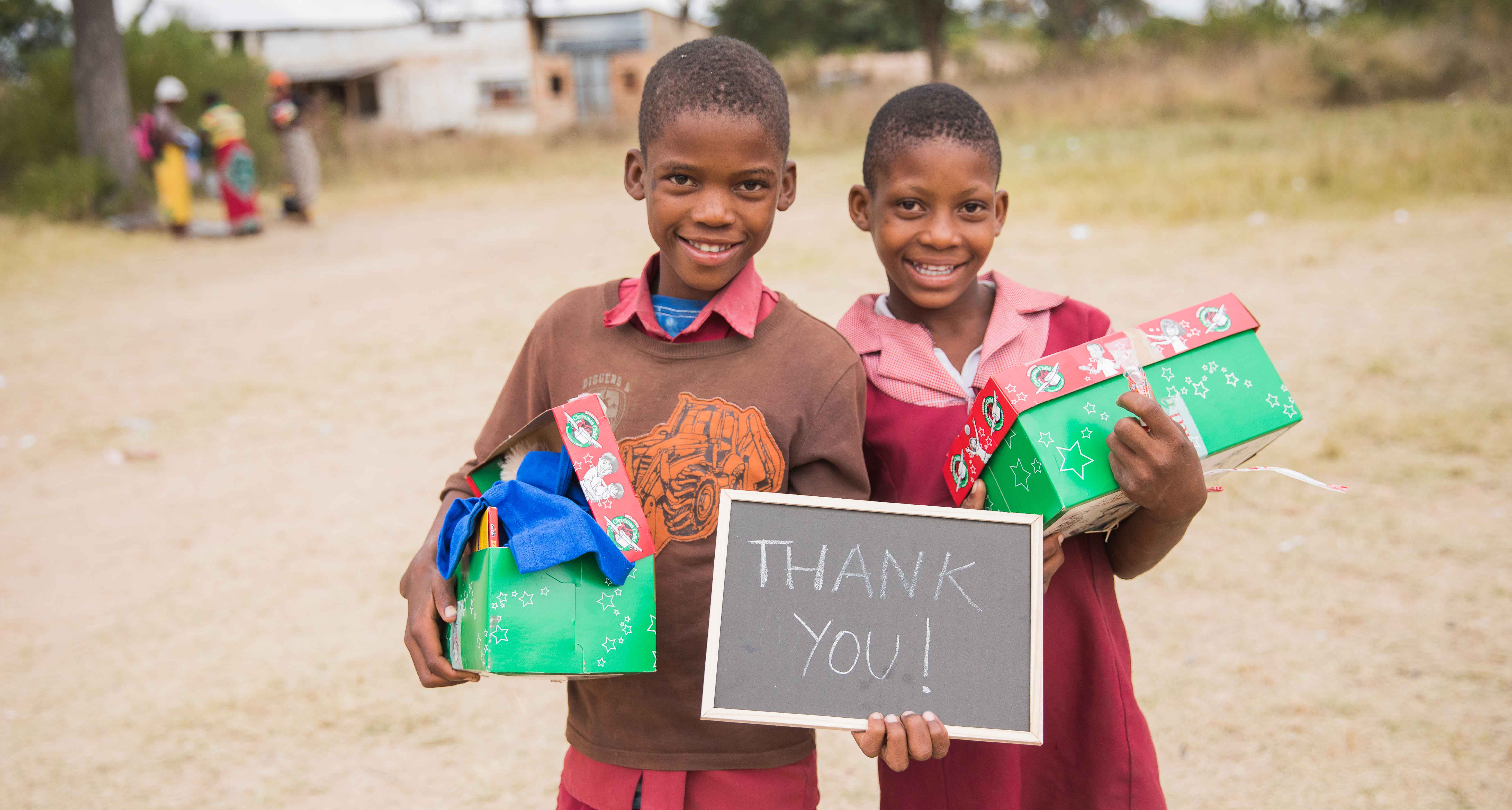 Children holding shoeboxes and blackboard with thank you