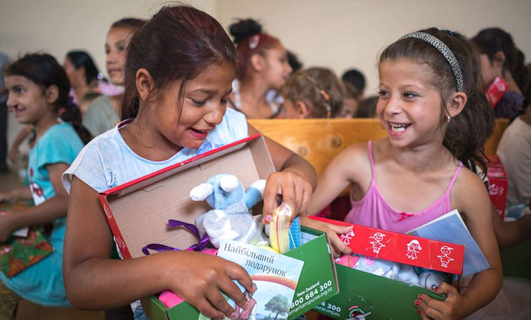 Girls laughing as they explore their shoeboxes