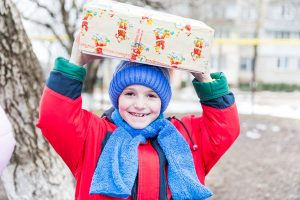 Smiling child in red coat and blue hat and scarf holding shoebox on head