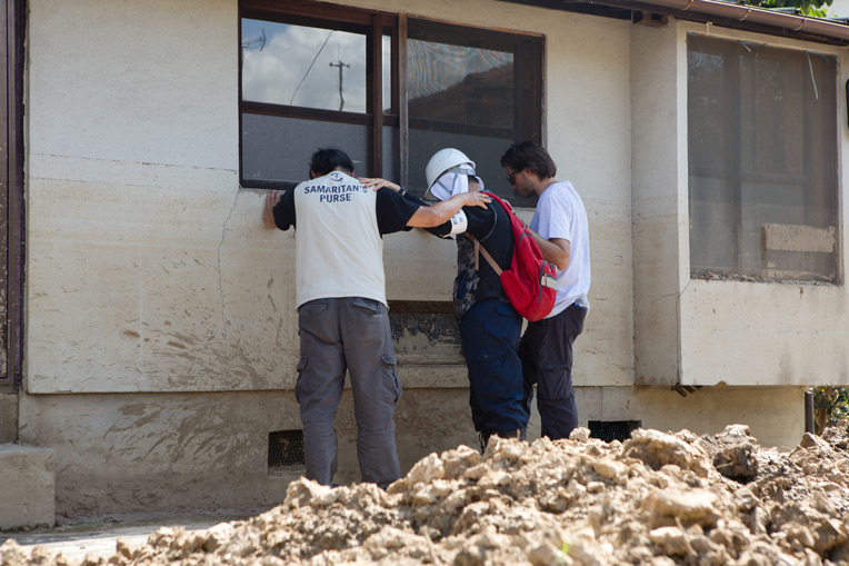 Members of our Disaster Assistance Response Team pray with a worker helping clean up flooded homes in Southern Japan