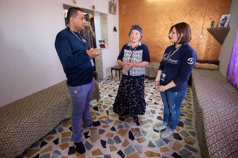Anna (centre) and the Samaritan's Purse staff talk and pray together in her newly restored home.