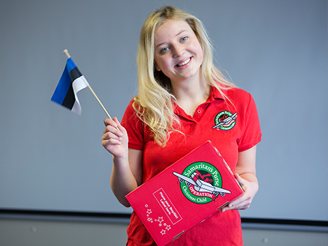 Shoebox recipient Pille holding a shoebox and the Estonian Flag