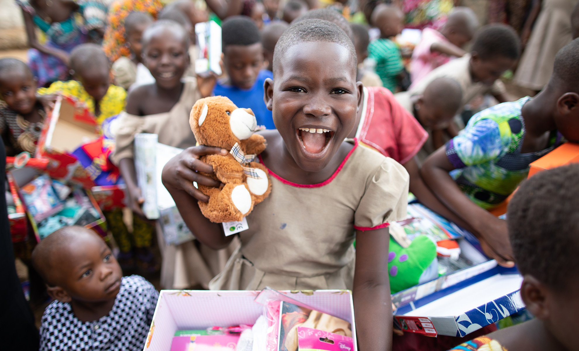 Laughing girl holding teddy and shoebox