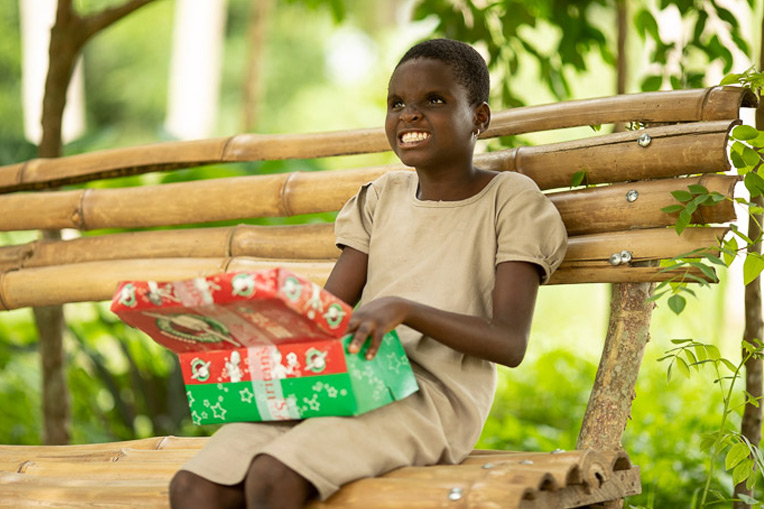JOSEPHINE ENJOYS THE SPECIAL GIFTS SHE RECEIVED DURING A SHOEBOX GIFT DISTRIBUTION IN TOGO.