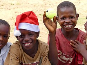 Children receive Santa hat and tennis ball