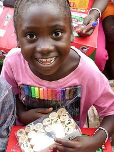 Girl receives pens in shoebox