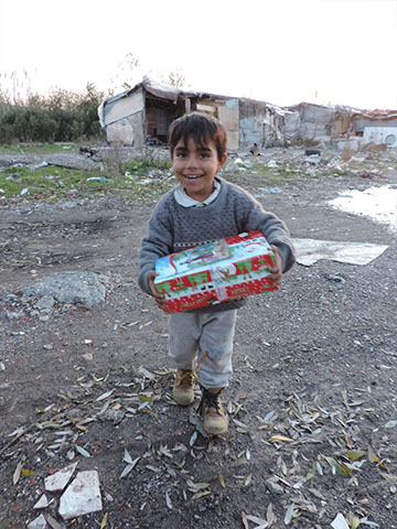 Little boy smiles with shoebox gift