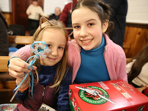 Two girls smile with gifts