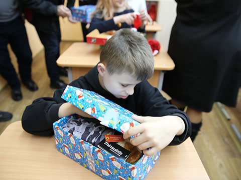 Boy with visual impairment feels his shoebox gifts
