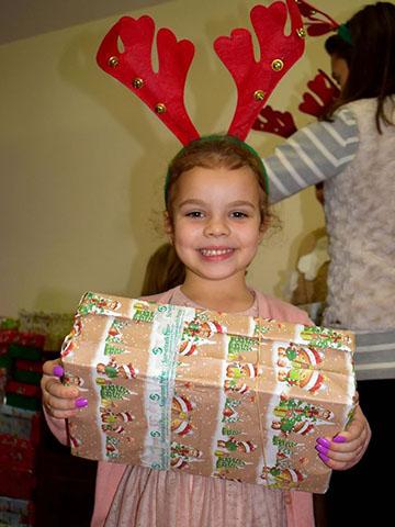 Girls with shoebox gift and reindeer antler