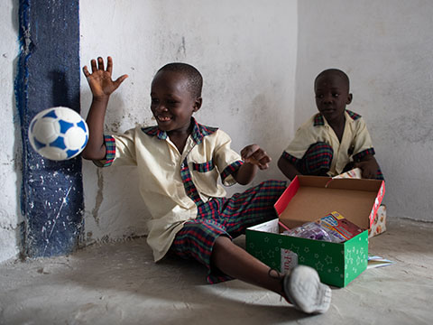 boy plays with football from shoebox gift
