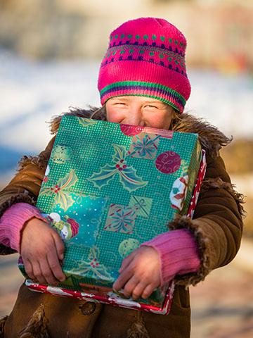 girl hugs shoebox gift