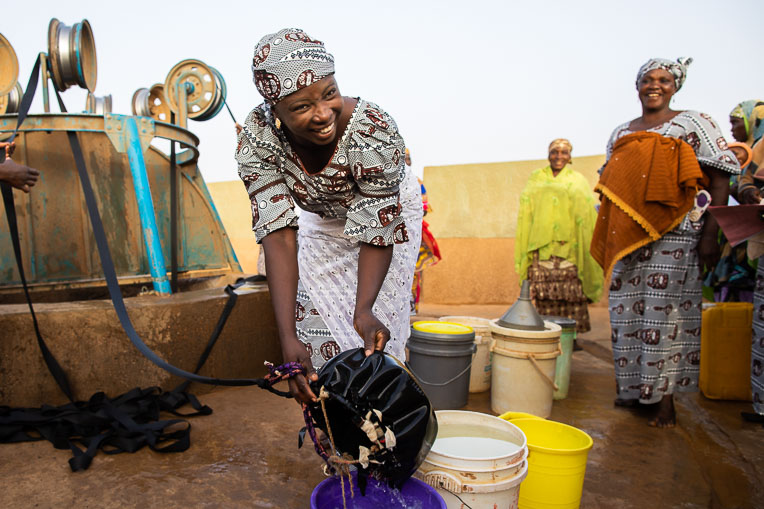 A woman in Niger gathers water at a well installed by Samaritan's Purse.