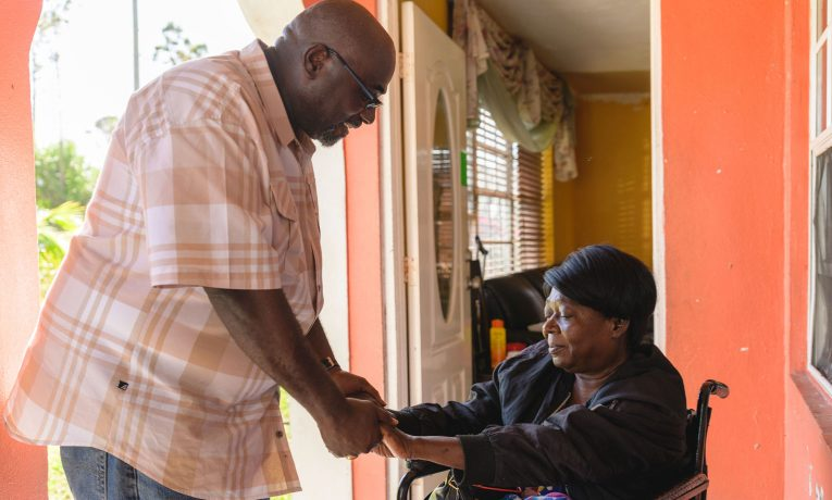 Pastor Sidney McIntosh prays with Laurene Newbold after Samaritan's Purse repaired her roof.