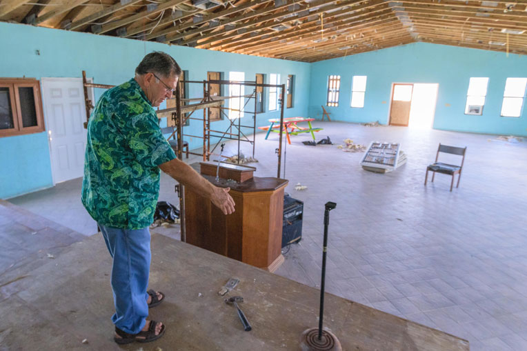 Pastor Robinson Weatherford points out the repairs that Samaritan's Purse did to the sanctuary of International Gospel Mission.
