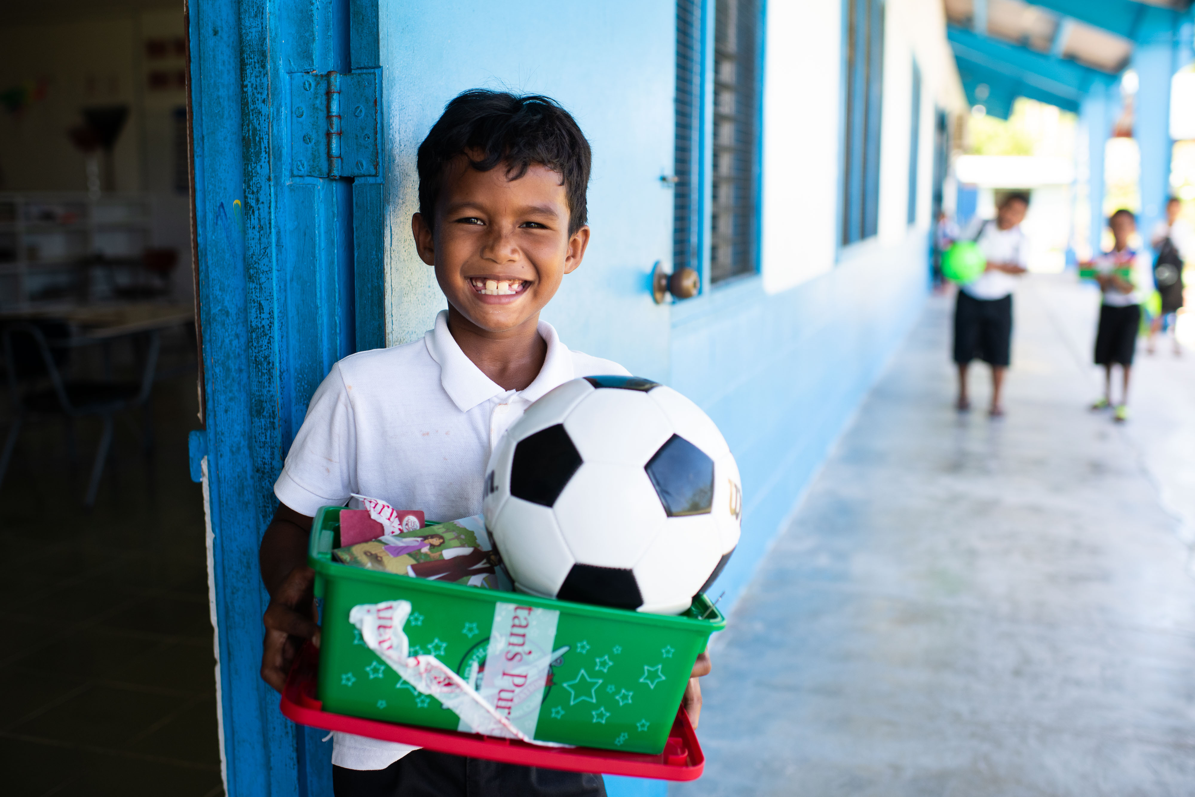 """A BOY FROM PELELIU ISLAND CELEBRATES THE """"WOW"""" TOY IN HIS GIFT-FILLED SHOEBOX."""