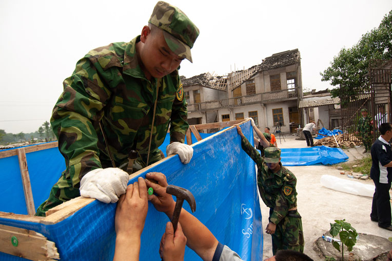 Local residents and Chinese military constructed emergency shelters with plastic sheeting and other materials provided by Samaritan's Purse.