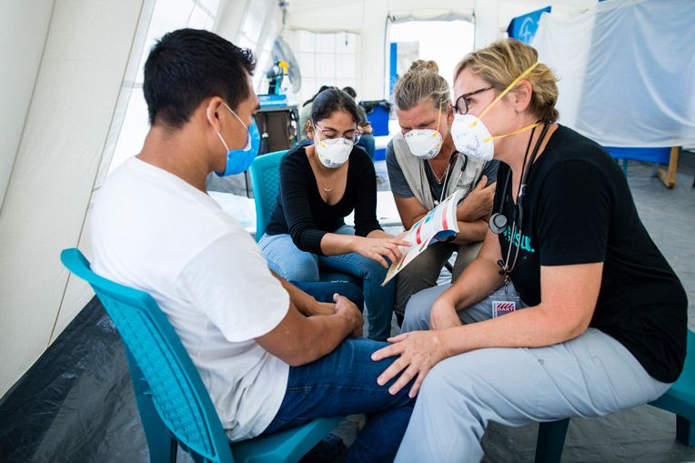 Physicians Assistant Gwen Miller and Nurse Kathy Mazzella share the Gospel through a translator with Israel at our Emergency Field Hospital.